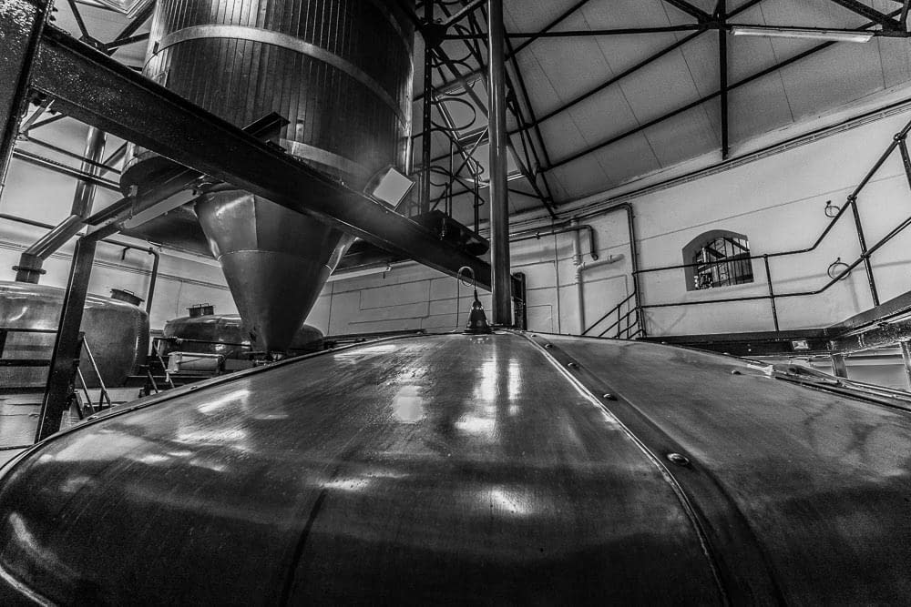 The two copper kettles (rear), the grist bin (top) and the copper topped mash tun (bottom) at Bowmore Distillery.