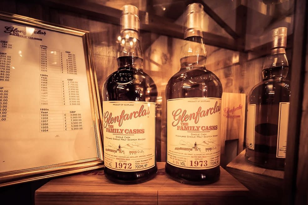 Photograph of 1972 and 1973 Glenfarclas Family Cask Edition bottles on display in the Glenfarclas Distillery Visitor Centre.