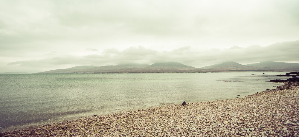 Looking across the sound from Islay to Jura paps on a pebbled beach