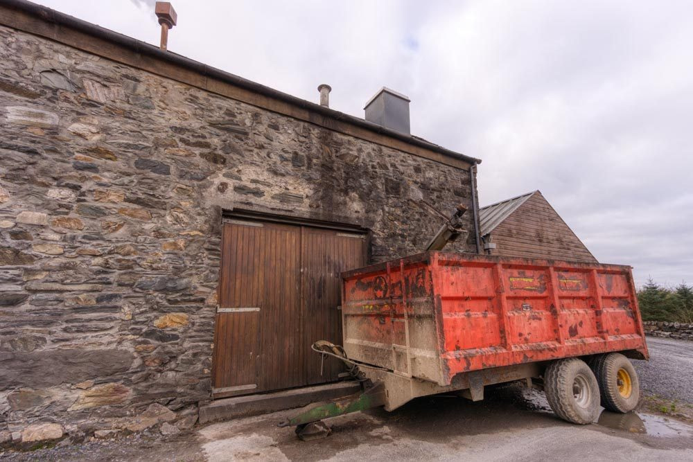 Red draff trailer parked against the stone wall of the still/mash house at Kilchoman Distillery