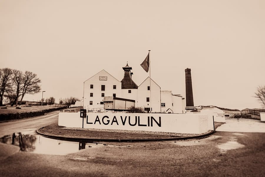 Sepia toned black and white photograph of Lagavulin Distillery, Islay, Scotland. photograph which shows the front of the distillery, the Lagavulin sign and the post box.