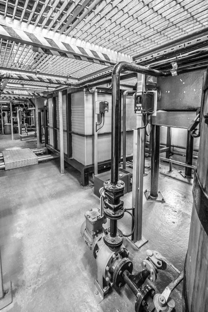 Receivers and pipe-work underneath the Wash and Spirit Stills at Kilchoman Distillery. Black and white photograph