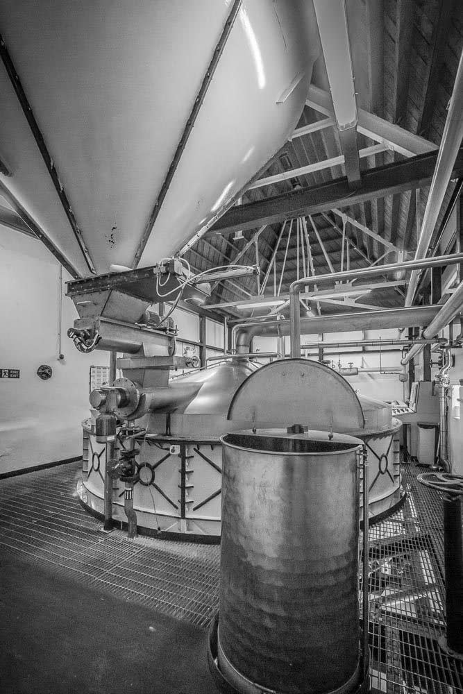 The grist hopper (top) is used to funnel grist into the mash tun. Noted in the foreground is the underback tank where Ardbeg stores the liquid (wort) resulting from the mash cycle, before transferring it to a washback.